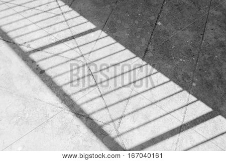 Shadow of the steel handrail on the concrete floor.