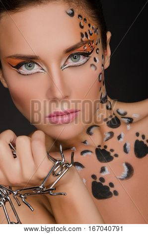 beautiful woman with face art and spines on dark background