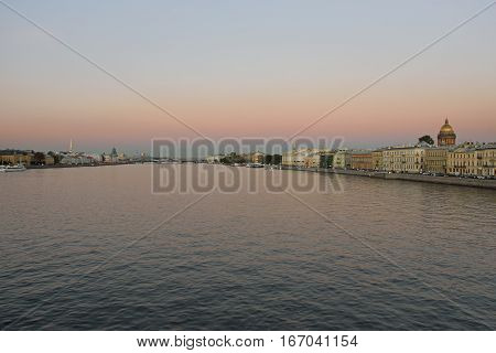 View of the Neva river, Palace bridge, the English embankment, St. Isaac's Cathedral with Blagoveshenskaja bridge on a summer evening in St. Petersburg.