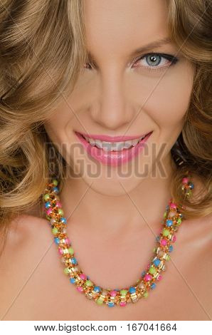 portrait of young smiling woman with necklaces on neck