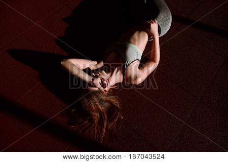 Top View Portrait Of A Young Woman Lying On At Gym . Female Wearing Fitness Outfit Lying Down