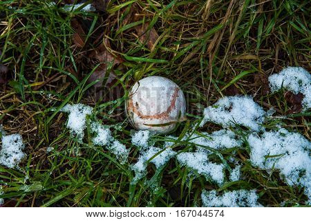 Tennis ball in rot and snow on wet grass