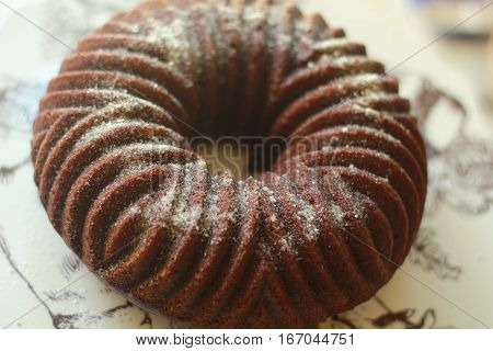 This pumpkin spice cake ring is molded with a bundt cake mold and has some powdered sugar sprinkled on it.