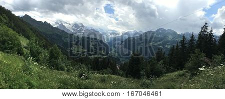 Panorama with valley and snow caps on mountain peaks