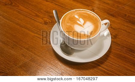 Cup of cappuccino coffee on brown wooden table. Above view. Vintage brown color.