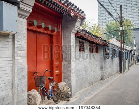 Beijing, China - Oct 30, 2016: Traditional Chinese home entrance in typical red color and design. Such architecture style is common in Old Beijing streets or alleys called Hutongs.