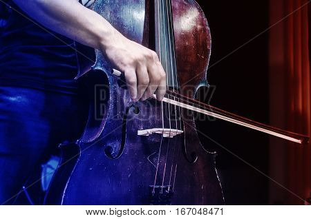 Musician cello. Cellist. Bass player. Hand with a bow on the strings of a wooden musical instrument.