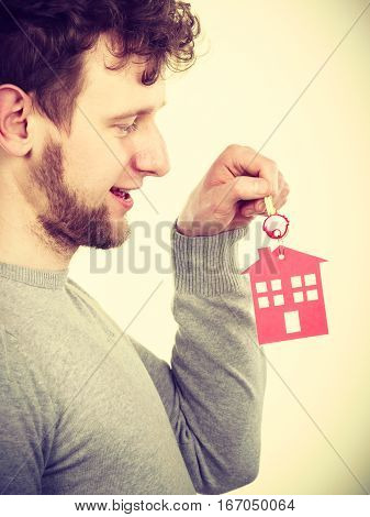 Security household access rent real estate concept. Man with house pendant. Young male with home shape keyring.