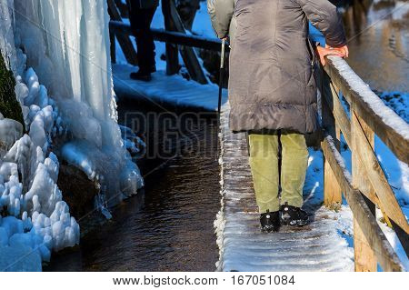 Older Couple Walking At A Frozen Waterfall