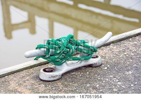 green rope wrapped around boat cleat on marina walkway with lake water reflection