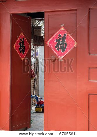 Beijing, China - Oct 30, 2016: Traditional Chinese home entrance around Dong Cheng area, complete with knocker handles. Such architecture style is common in Old Beijing streets or alleys called Hutongs. This entrance is on Cuihua Hutong. The Chinese chara