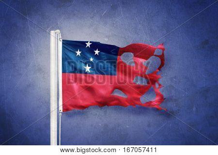 Torn flag of Samoa flying against grunge background