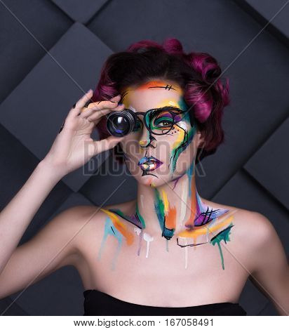 close-up fashion faceart portrait of young girl with art painting and lens glass. Amazing creative picture with surrealistic face. Painted background