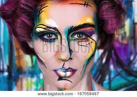 close-up fashion faceart portrait of young girl with art painting. Amazing creative picture with surrealistic face. Painted background