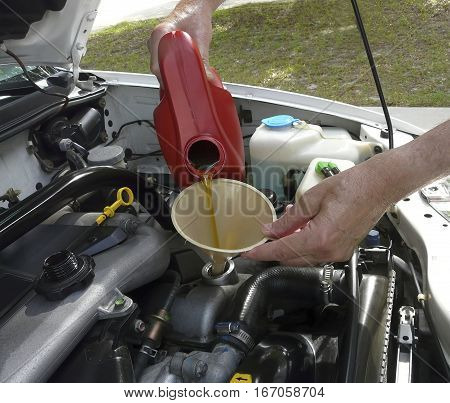 Man adding oil with a funnel from the right side of a white car after an oil change. Dipstick and cap are nearby.
