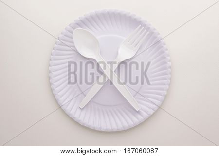 crossing spoon and fork on paper disk on white paper background in concept of abstain