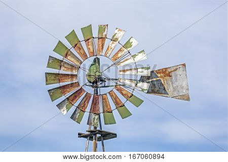 A rusty metal windmill with pale green blades stands against a cloudy blue Midwestern sky.