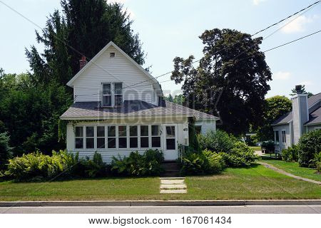 HARBOR SPRINGS, MICHIGAN / UNITED STATES - AUGUST 4, 2016: A white home with ferns Fourth Street in Harbor Springs.