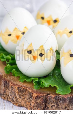 Little chicken in nest deviled eggs served with salad on wooden board vertical