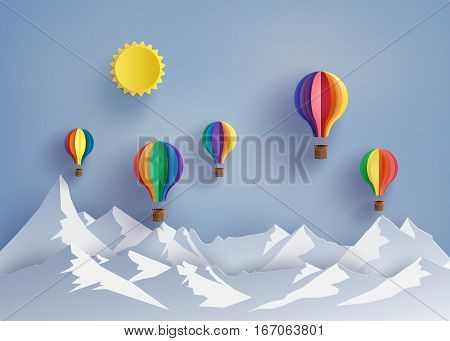 Origami made colorful hot air balloon flying over the moutain with sun.paper art style.