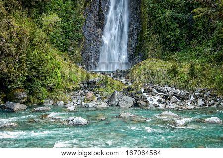 Aqua water at the bottom of the Thunder Creek Falls near Wanaka on the South Island of New Zealand