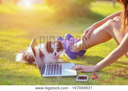 close up of woman hands and relaxing with puppy at park
