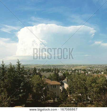 Huge white cloud and blue sky over city of Calgary in summer. Sunlight behind thunder cloud. Houses and trees in foreground.