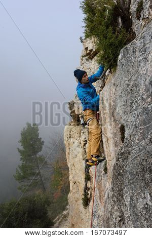 Rock climber ascending a challenging cliff. Extreme sport climbing. Freedom, risk, challenge, success