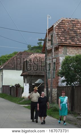 Rametea,Romania - June 27,2007: Group of Transylvanian saxon villagers returning to their home from the field work, on a cloudy summer day, late in the afternoon in Rametea,Romania on 27 June 2009.