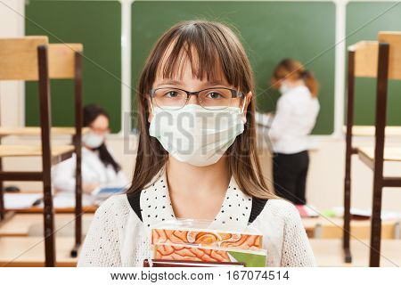 School girl in medical face mask are learning in the half empty classroom during epidemic of flu.