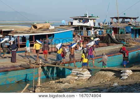 MANDALAY, MYANMAR - DECEMBER 21, 2016: Stevedores unloading a river barge in the port of Mandalay