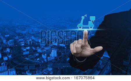 Businessman pressing motor bike icon over modern city tower street and expressway Business delivery service concept