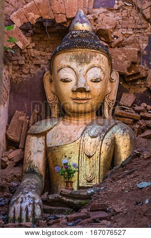 Buddha statue hiding in the ruins of the Shwe Inn Dein Pagoda at Inle Lake Shan state in Myanmar