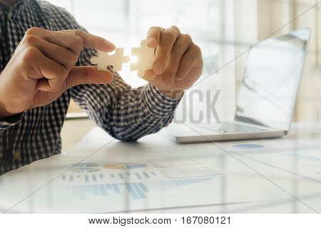 Business man hands connecting jigsaw puzzle. Business solutions success and strategy concept. Businessman concept. Close up photo with selective focus.