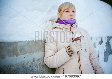 Young Woman Dressed In Warm Clothes Drinking Takeaway Coffee From The Cup On The Street In Winter