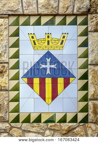 Calafell Spain - May 22 2016: Calafell town Coat of arms on the old stone wall Catalonia Tarragona region Spain
