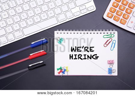 WE'RE HIRING WORD WITH KEYBOARD COMPUTER ON BLACK BACKGROUND