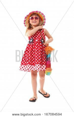 Little girl is dressed in red summer dress beach shoes sunglasses and hat. She is having a bright beach bag. She is going to go on a beach.