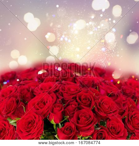 Bouquet of fresh dark red rose buds with over bokeh fesive background