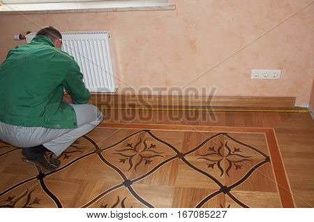 Repairman Installing Skirting Board Oak Wooden Floor. Flooring with Wooden Batten Repair. Parquet flooring.
