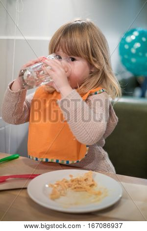 Little Kid Drinking Water Glass At Pizza Restaurant Looking