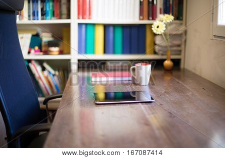 digital tablet cup of coffee book vase with flowers on wooden table black seat and library in office next to window nobody