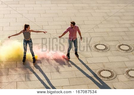 Couple on rollerblades outdoors. Pink and yellow smoke. Colorize this world.