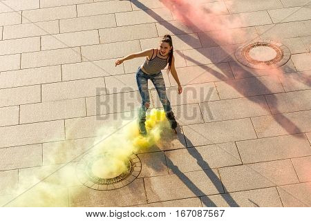Young woman on rollerblades. Smoke coming from roller skates. Life needs more colors.