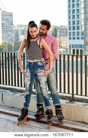 Couple on inline skates. Man standing behind woman. Bold and confident.