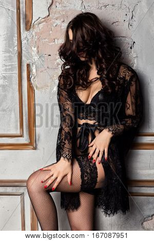 fashion sexy young woman in black lacy lingerie and stockings posing on old wall.