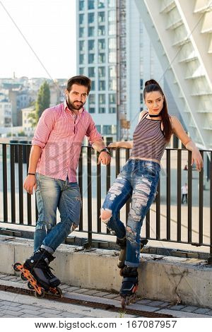Couple on rollerblades outdoor. People standing on city background. Young, bold and stylish.
