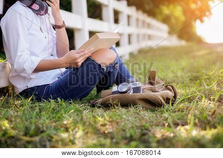 Asian woman relaxing outdoors looking happy and reading a book . Relaxing concept. Retro filter effectsoft focusselective focus.