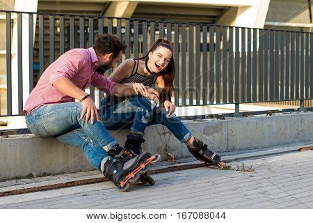 Two people on rollerblades sitting. Young female laughing. Funny things that you say.