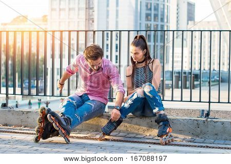 Young couple on rollerblades sitting. Two people on urban background. First date in the city.